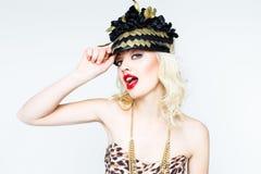 Portrait de belle jeune femme blonde dans le chapeau exagéré sur le fond blanc image stock