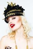 Portrait de belle jeune femme blonde dans le chapeau exagéré sur le fond blanc photographie stock libre de droits