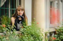 Portrait de belle jeune femme dans la robe blanche avec la rose de noir Photographie stock libre de droits