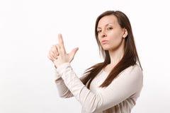 Portrait de belle jeune femme sûre dans des vêtements légers regardant la caméra tenant des mains comme l'arme à feu d'isolement  photo stock