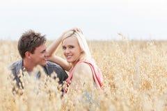Portrait de belle jeune femme se reposant avec l'ami parmi le champ Photo stock