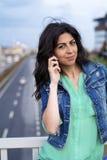 Portrait de belle jeune femme se reposant sur le pont au-dessus de la route et parlant au téléphone Photo libre de droits