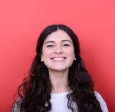 Portrait de belle jeune femme souriant sur le fond rouge Photos stock