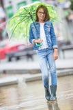 Portrait de belle jeune fille de la pr?adolescence avec le parapluie sous le ressort ou la pluie d'?t? photo libre de droits