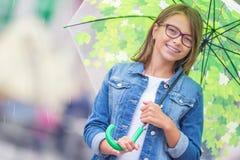 Portrait de belle jeune fille de la pr?adolescence avec le parapluie sous le ressort ou la pluie d'?t? images libres de droits