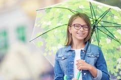 Portrait de belle jeune fille de la pr?adolescence avec le parapluie sous le ressort ou la pluie d'?t? image libre de droits