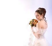 Portrait de belle jeune mariée dans le voile avec un bouquet, regardant Image libre de droits