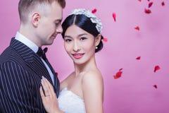 Portrait de belle jeune mariée se tenant avec le marié sur le fond rose Photo libre de droits