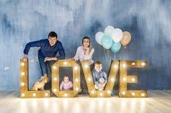 Portrait de belle maman, de papa et de beaux enfants dans le studio Photos stock