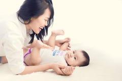 Portrait de belle maman jouant avec ses 6 mois de bébé dedans Photo stock