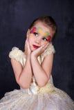 Portrait de belle petite fille dans des lèvres rouges de robe blanche avec le visage peint au fond foncé Image libre de droits