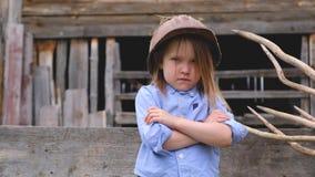 Portrait de belle petite fille dans le casque bleu de construction de chemise et de cru banque de vidéos