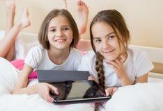 Portrait de belles adolescentes se trouvant sur le lit et tenant la tablette numérique Images stock