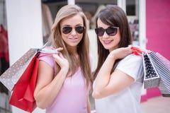 Portrait de belles femmes dans des lunettes de soleil tenant des paniers Photos libres de droits