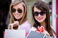 Portrait de belles femmes dans des lunettes de soleil tenant des paniers Photographie stock libre de droits