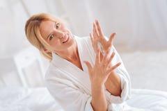 Portrait de blonde avec plaisir cette crème de propagation en main Photos stock