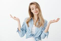Portrait de blonde belle insouciante dans l'équipement à la mode, soulevant les paumes répandues et gesticulant avec le sourire h photos libres de droits