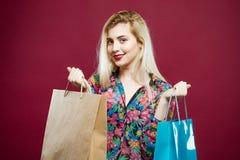 Portrait de blonde mignonne avec deux sacs en papier dans la chemise colorée sur le fond rose dans le studio Femme de sourire ave image stock