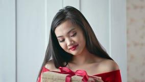 Portrait de boîte-cadeau asiatique de sourire de participation de jeune femme avec le ruban rouge clips vidéos