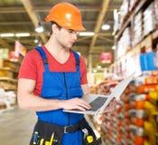 Portrait de bricoleur avec l'entrepôt fonctionnant d'ordinateur portable Photographie stock libre de droits