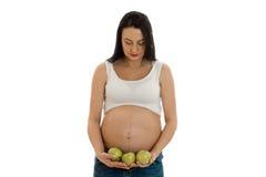 Portrait de brune enceinte dans les pommes blanches de vert de twith de chemise dans des mains regardant vers le bas d'isolement  Image stock