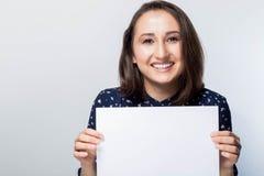 Portrait de brune heureuse avec l'annonce regardant l'appareil-photo, femme de sourire tenant le panneau blanc de signe photographie stock libre de droits