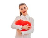 Portrait de brune heureuse dans l'amour avec le coeur rouge d'isolement sur le fond blanc concept du ` s de valentine de saint Co Photographie stock