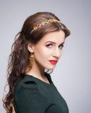 Portrait de brune magnifique utilisant la couronne et les boucles d'oreille d'or de luxe photographie stock libre de droits