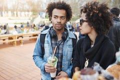 portrait de Côté-vue de l'ami à la peau foncée attirant sérieux avec la coiffure Afro marchant sur le festival de nourriture avec Image libre de droits