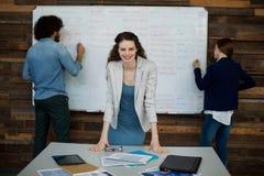 Portrait de cadre commercial de sourire se penchant sur la table tandis que collègue travaillant à l'arrière-plan Images stock