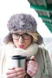 Portrait de café de soufflement de femme dans le récipient isolé de boissons pendant l'hiver images libres de droits