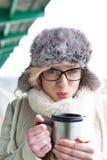 Portrait de café de soufflement de femme dans le récipient isolé de boissons pendant l'hiver photo stock