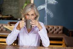 Portrait de café potable de femme supérieure tout en se reposant à la table Photo libre de droits