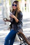 Portrait de café potable et d'employer de belle fille son mobile Photographie stock