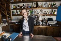 Portrait de caissier féminin de sourire au compteur dans le restaurant photographie stock