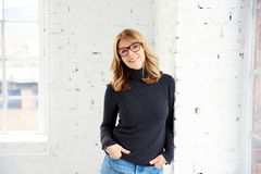 Portrait de chandail et de jeans de cou de petit pain de port de femme attirante tout en regardant la cam?ra et le sourire photographie stock