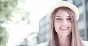 Portrait de chapeau de port de femme assez gaie dans le jour chaud ensoleillé de temps banque de vidéos