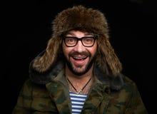 Portrait de chapeau de fourrure de port d'homme gai sûr image stock