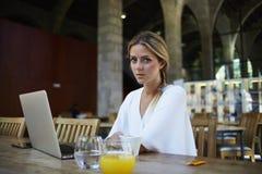 Portrait de charmer la femelle de la Suède employant le filet-livre pour le travail à distance tout en se reposant dans l'intérie Images stock