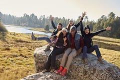 Portrait de cinq amis s'asseyant sur une roche dans la campagne Images libres de droits
