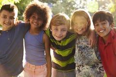 Portrait de cinq enfants ayant l'amusement dehors ensemble Images libres de droits