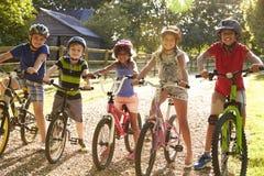 Portrait de cinq enfants sur le tour de cycle ensemble Image libre de droits