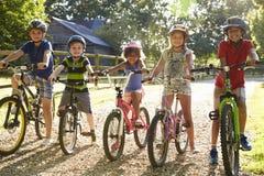 Portrait de cinq enfants sur le tour de cycle ensemble Images libres de droits