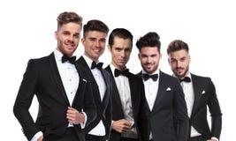 Portrait de cinq hommes attirants portant des tuxedoes se tenant en lin Images stock