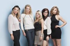 Portrait de cinq jeunes amis féminins se tenant ensemble sur le fond bleu-clair Photo libre de droits