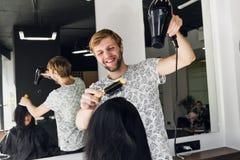 Portrait de coiffeur heureux tenant le peigne et le dessiccateur de coup dans le salon photos stock