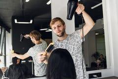 Portrait de coiffeur heureux tenant le peigne et le dessiccateur de coup dans le salon image libre de droits