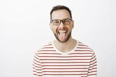 Portrait de collègue adulte drôle beau en verres noirs, collant la langue et souriant joyeux, étant insouciant image libre de droits