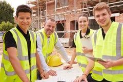 Portrait de constructeur On Building Site avec des apprentis Photos stock