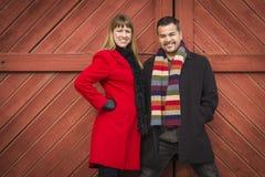 Portrait de couples de métis dans l'habillement d'hiver contre la porte de grange Photos stock
